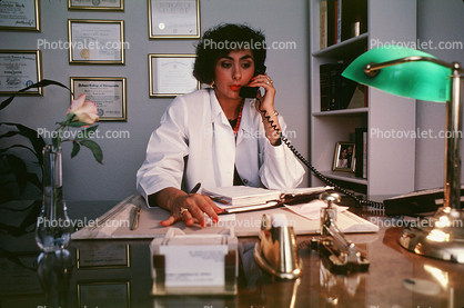 Female Doctor at her desk chatting on the phone