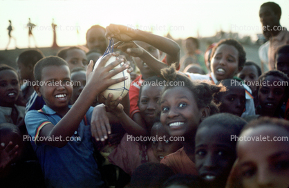 Children holding up an Ostrich Egg, smiles, funny, fun, Exuberance