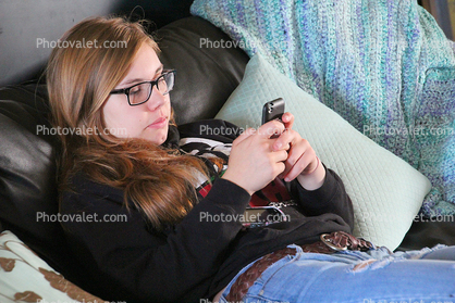 Teen Girl playing with her hand held device, I phone, Iphone, I-phone, cell phone, hand held device, hand, fingers, monitor, cloud computing, Iphone-4s
