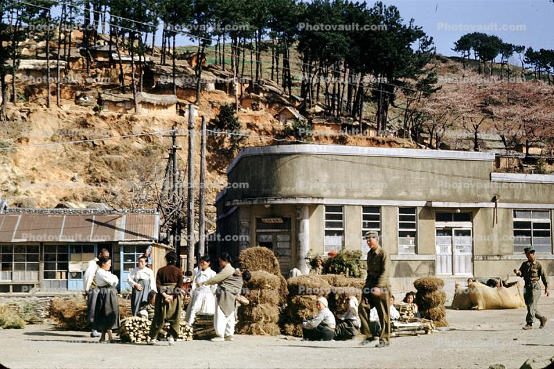 Building, hill, houses, women, men, Pusan, April 1953