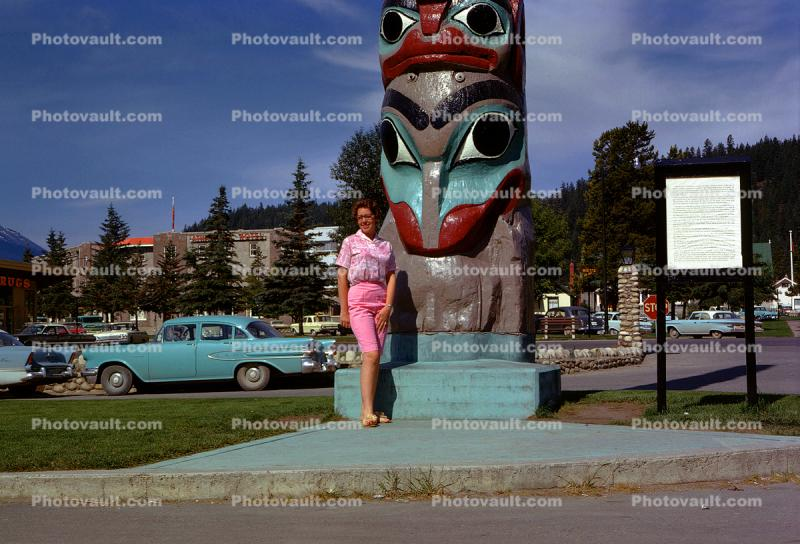 Woman Poses in front of a Totem Pole, cars, 1950s