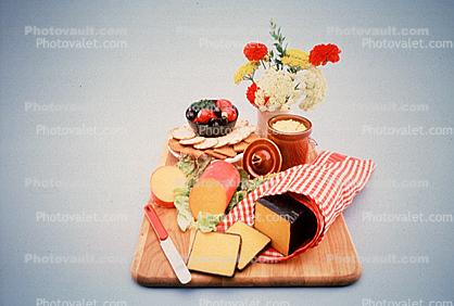 cheese plate, knife, crackers, cutting board