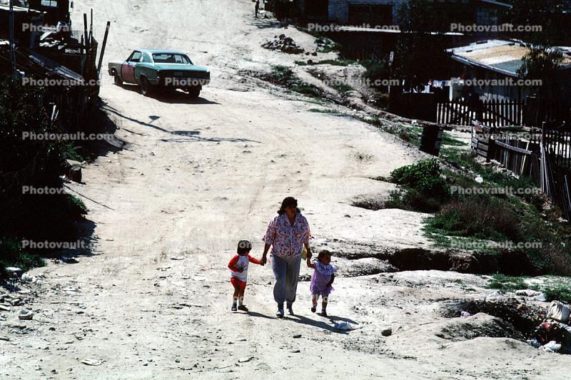 mother, children, walking, car, dirt street, Colonia Flores Magone
