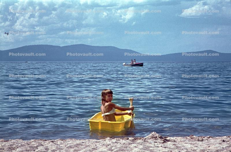 Girl on a tiny rowboat, paddle, beach, sand, Lake Tahoe, 1960s