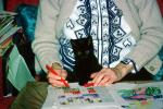 Black Cat on grandmas lap, puzzle, hands