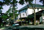 Stores, cypress trees, cars, building, downtown Carmel, 1960s, CNCV01P01_01