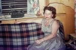 Woman sitting on a Sofa, inside a trailer, windows, 1940s