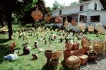 frontyard full of figurines, elfs, cats, mother goose, front yard, hammock, home, house, baskets