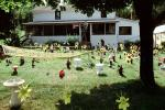 frontyard full of figurines, elfs, cats, mother goose, front yard, hammock, home, house