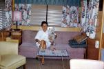 Woman sits on a Sofa, couch, lamp, coffee table, mod, Dog, lampshade, Trailer Home, curtains, 1960s