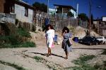 women walking, dirt street, homes, houses, Colonia Flores Magone