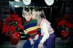 girl kisses boy, brother, siblings, stockings, fireplace, brick, poinsettia