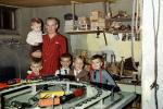 Boys with their Christmas model train set, basement, 1950s