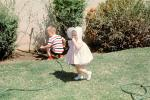 Girl with Bonnet, Backyard, Hose, Boy, Lawn, April 1965, 1960s, PHEV01P01_15