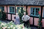 Woman and Man in front of their house, thatched roof, flowers, 1950s, Sod, PORV26P10_03