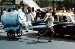 Man pulling on a cart, water, barrel, taxi cab, car, on the Streets of Mumbai