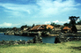 harbor, stone walls, grass thatched huts, homes, houses, roofs, building