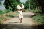 Man Walking Down a Dirt Road Carrying a Heavy Load, India, PDCV01P02_17