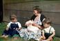 Woman with her sons, swaddled baby, floral dress, Easter Basket, smiles, 1950's, PHEV01P01_19