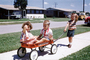 Greyhound pull wagon, boy, girl, brother, sister, sidewalk, suburban, suburbia, cars, 1960's, PLGV03P04_18